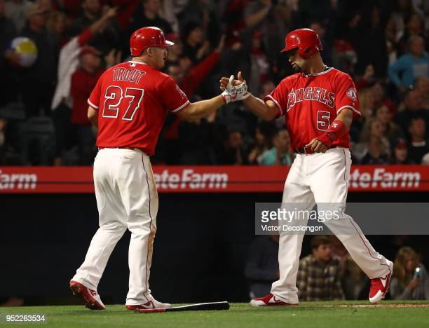 Mike Trout and Albert Pujols of the Los Angeles Angels of Anaheim celebrate in the infield after scoring on a triple by teammate Andrelton Simmons to...