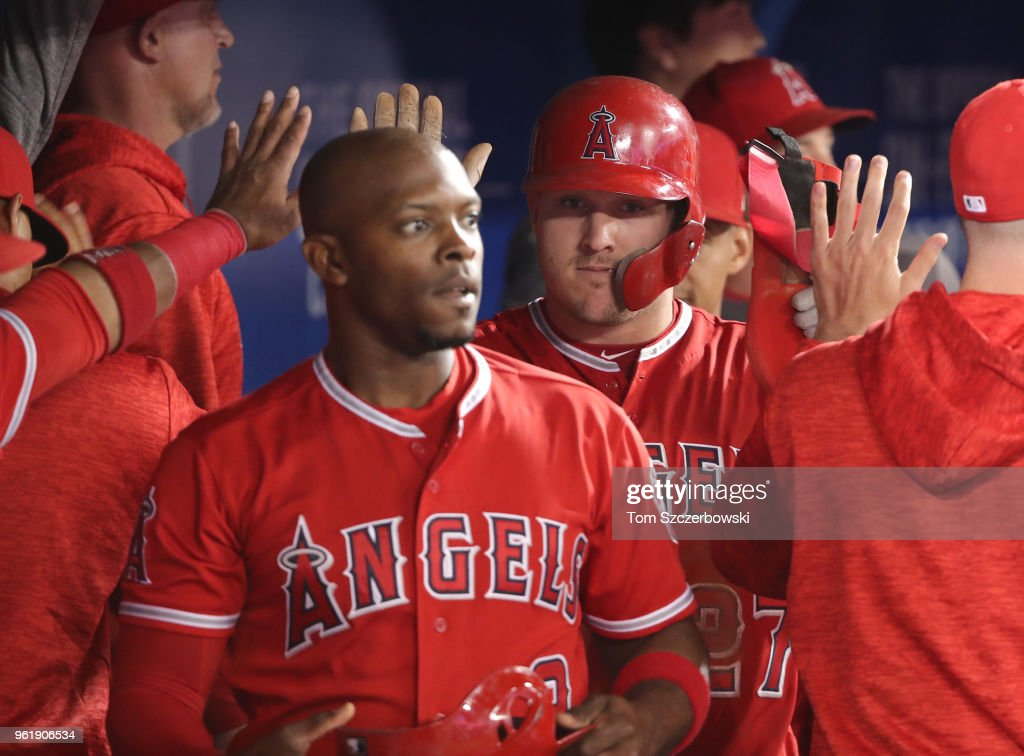 Mike Trout #27 and Justin Upton #8 of the Los Angeles Angels of Anaheim are congratulated by teammates in the dugout after scoring runs in the ninth inning during MLB game action against the Toronto Blue Jays at Rogers Centre on May 23, 2018 in Toronto, Canada.