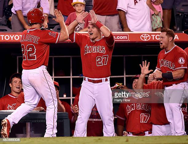 Mike Trout and Kole Calhoun of the Los Angeles Angels react to the two run homerun of Conor Gillaspie to take a 43 lead over the Cleveland Indians...