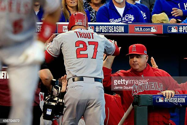 Mike Trout celebrates with Mike Scioscia of the Los Angeles Angels after hitting a home run in the first inning against the Kansas City Royals during...