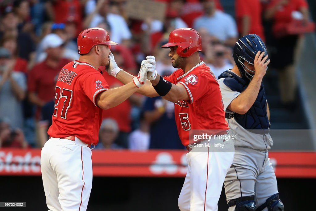 Mike Trout #27 congratulates Albert Pujols #5 of the Los Angeles Angels of Anaheim after his two-run homerun while David Freitas #36 of the Seattle Mariners looks on during the first inning of a game at Angel Stadium on July 12, 2018 in Anaheim, California.