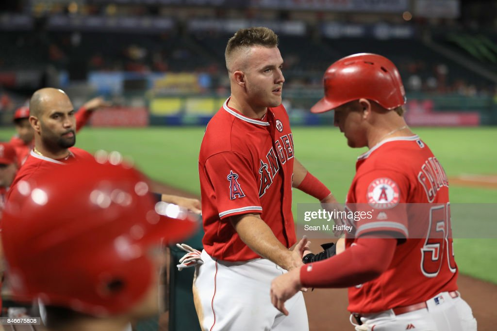 Mike Trout #27 congratulates Kole Calhoun #56 after he scored on an RBI double hit by Andrelton Simmons #2 of the Los Angeles Angels of Anaheim during the first inning of a game against the Houston Astros at Angel Stadium of Anaheim on September 13, 2017 in Anaheim, California.