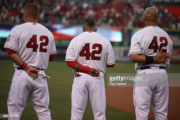 Mike Trout Erick Aybar and Albert Pujols of The Los Angeles Angels stand at attention during the playing of the National Anthem while wearing number...