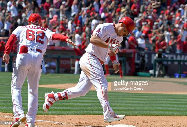 Mike Trout is congratulated by Jesus Feliciano of the Los Angeles Angels of Anaheim as rounds the bases after hitting a grand slam home run in the...