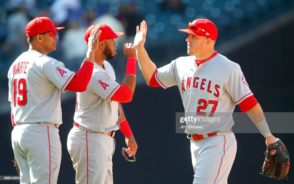 Mike Trout #27, Luis Valbuena #18 and Jefry Marte #19 of the Los Angeles Angels of Anaheim celebrate after defeating the New York Mets at Citi Field on May 21, 2017 in the Flushing neighborhood of the Queens borough of New York City.