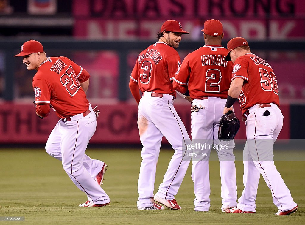 Mike Trout #27 of the Los Angeles Angels celebrates a 5-4 win over the Cleveland Indians wth David DeJesus #3, Erick Aybar #2, and Kole Calhoun #56 at Angel Stadium of Anaheim on August 3, 2015 in Anaheim, California.