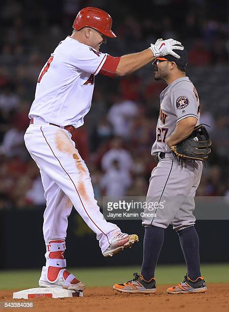 Mike Trout of the Los Angeles Angels grabs Jose Altuve of the Houston Astros on the head after he returned to second after sliding on the ground as...