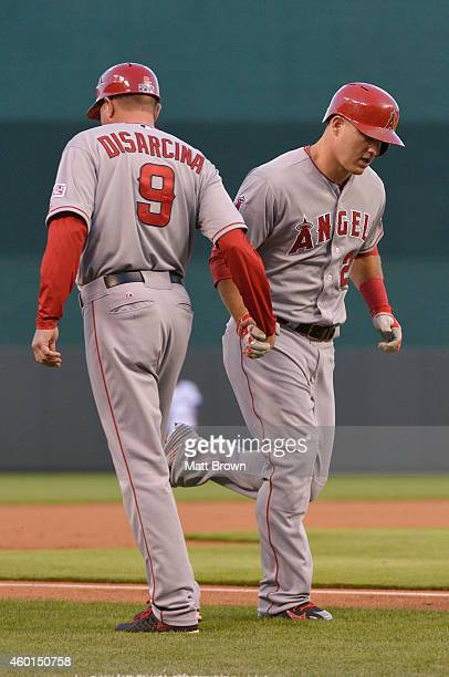 Mike Trout of the Los Angeles Angels high fives third base coach Gary DiSarcina after hitting a home run during game 3 of the American League...