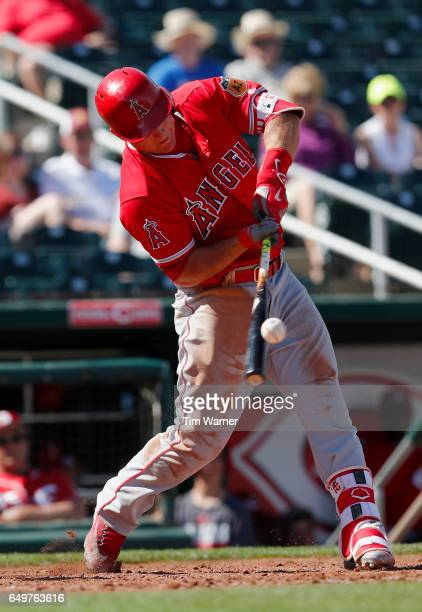 Mike Trout of the Los Angeles Angels hits a ground ball in the fourth inning against the Cincinnati Reds during the spring training game at Goodyear...