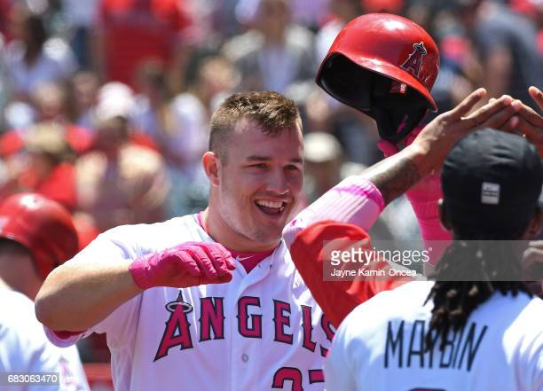 Mike Trout of the Los Angeles Angels is greeted in the dugout after a solo home run in the first inning of the game against the Detroit Tigers at...