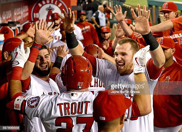 Mike Trout of the Los Angeles Angels is greeted in the dugout by Jett Bandy and Rafael Ortega after hitting a 2 run home run in the first inning of...