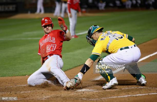 Mike Trout of the Los Angeles Angels is tagged out by Bruce Maxwell of the Oakland Athletics in the third inning at Oakland Alameda Coliseum on...