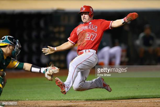 Mike Trout of the Los Angeles Angels is tagged out by Bruce Maxwell of the Oakland Athletics in the fifth inning at Oakland Alameda Coliseum on...