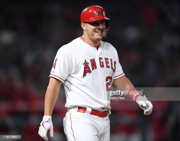 Mike Trout of the Los Angeles Angels laughs as he heads to first base after he is hit by a pitch during the seventh inning against the Oakland...
