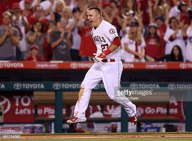 Mike Trout of the Los Angeles Angels of Anaheim celebrates as he runs home after hitting a game winning walk off home run to lead off the ninth...