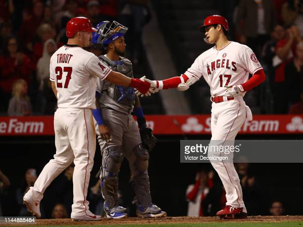 Mike Trout of the Los Angeles Angels of Anaheim congratulates teammate Shohei Ohtani at home plate after Ohtani hit a tworun homerun as catcher...