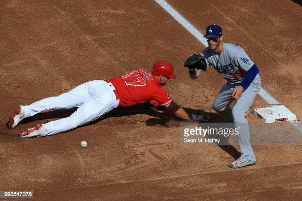 Mike Trout of the Los Angeles Angels of Anaheim dives back first base safely on a pick off attempt as Cody Bellinger of the Los Angeles Dodgers...
