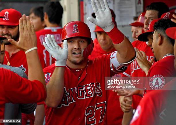 Mike Trout of the Los Angeles Angels of Anaheim gets high fives in the dugout after a solo home run in the first inning off James Shields of the...