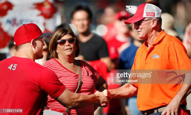 Mike Trout of the Los Angeles Angels of Anaheim greets family friend Bob Reed of Millville New Jersey before the start of the game against the...