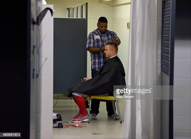 Mike Trout of the Los Angeles Angels of Anaheim has his hair cut by barber Lati Hayes in the clubhouse before the game against the Los Angeles...