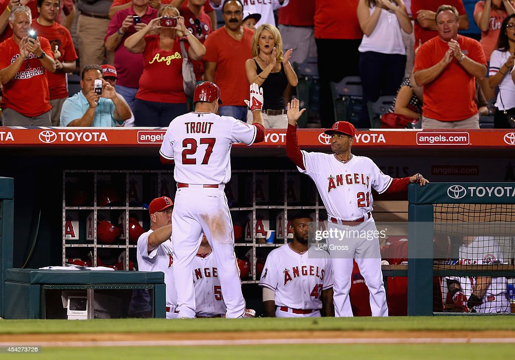 Mike Trout #27 of the Los Angeles Angels of Anaheim is congratulated by Dino Ebel #21 after hitting a solo home run in the seventh inning against the Miami Marlins at Angel Stadium of Anaheim on August 27, 2014 in Anaheim, California.