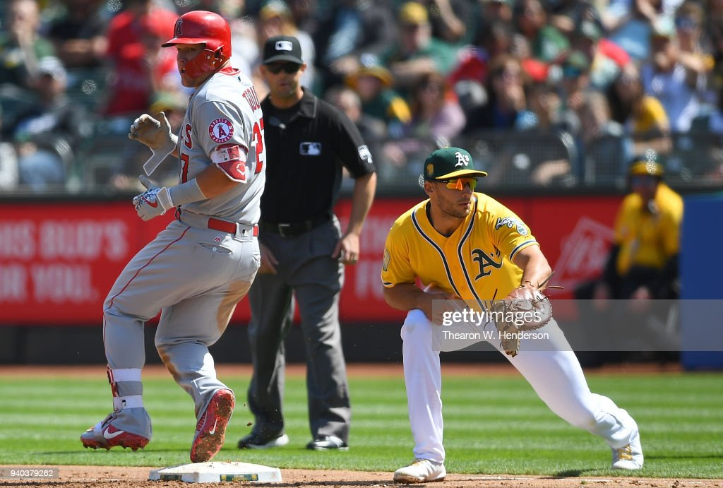 Mike Trout #27 of the Los Angeles Angels of Anaheim is safe at first base after striking out, beating the throw down to Matt Olson #28 of the Oakland Athletics in the top of the third inning of a Major League Baseball game at Oakland Alameda Coliseum on March 31, 2018 in Oakland, California.