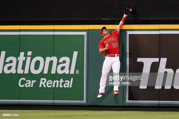 Mike Trout of the Los Angeles Angels of Anaheim is unable to hold onto a solo homerun hit by David Freitas of the Seattle Mariners during the third...