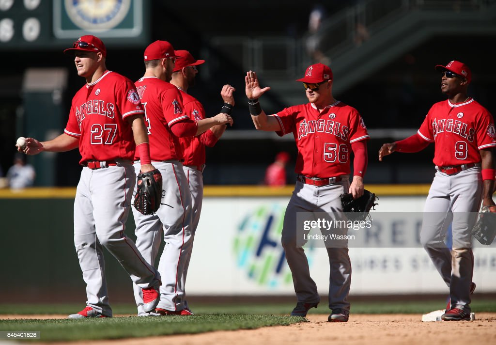 Mike Trout #27 of the Los Angeles Angels of Anaheim, Kole Calhoun #56 and Justin Upton #9 come in from the outfield to celebrate their 5-3 win over the Seattle Mariners at Safeco Field on September 10, 2017 in Seattle, Washington.