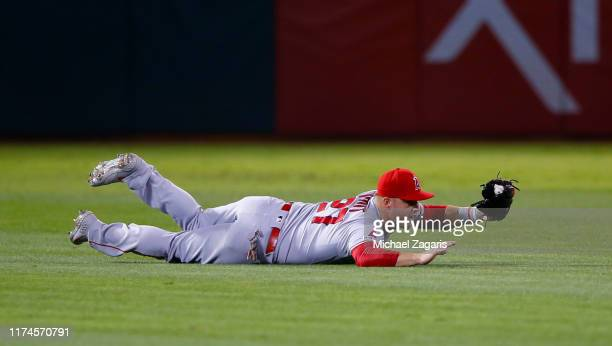 Mike Trout of the Los Angeles Angels of Anaheim makes a diving catch during the game against the Oakland Athletics at the OaklandAlameda County...