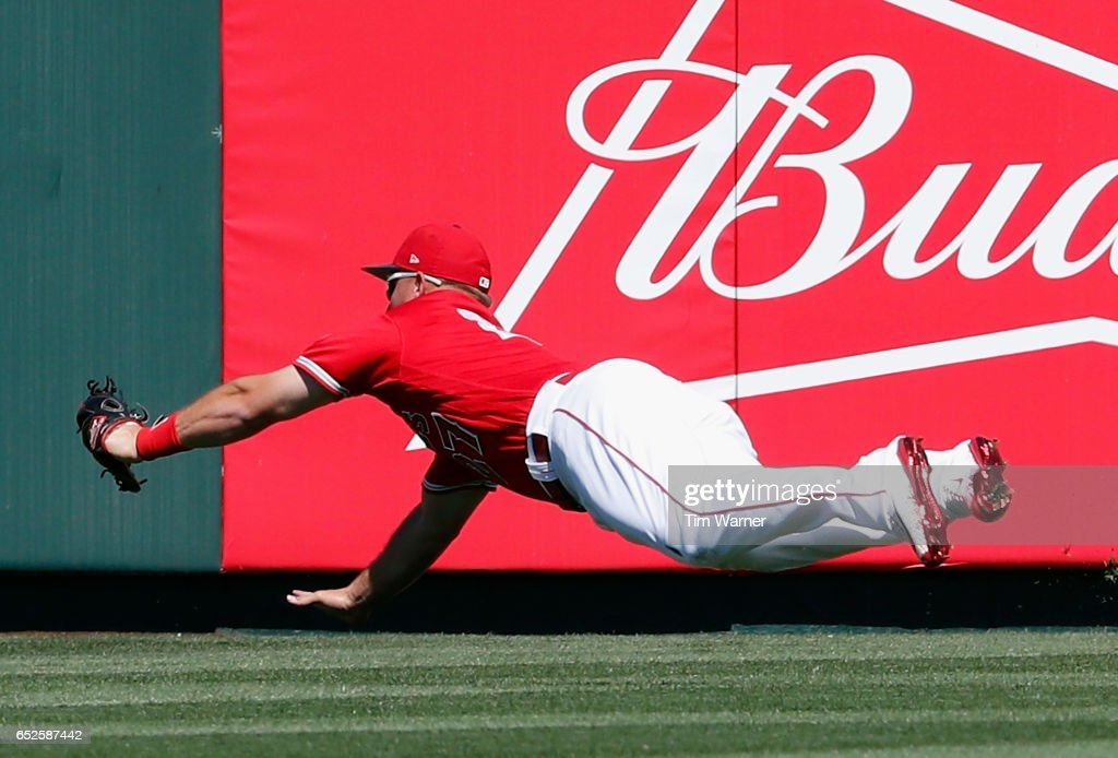 Mike Trout #27 of the Los Angeles Angels of Anaheim makes a diving catch in the first inning against the Seattle Mariners during a spring training game at Tempe Diablo Stadium on March 12, 2017 in Tempe, Arizona.