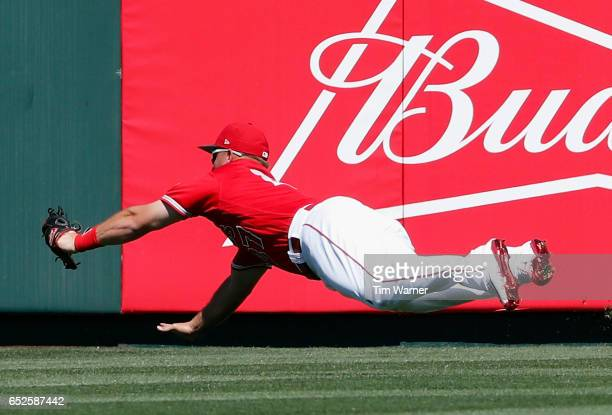 Mike Trout of the Los Angeles Angels of Anaheim makes a diving catch in the first inning against the Seattle Mariners during a spring training game...