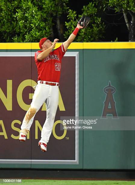 Mike Trout of the Los Angeles Angels of Anaheim makes a leaping catch at the wall as he steals a home run from Kyle Seager of the Seattle Mariners in...