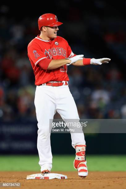 Mike Trout of the Los Angeles Angels of Anaheim motions to the umpire at second base after hitting a double during a game against the Cleveland...