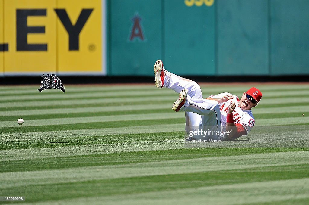 Mike Trout #27 of the Los Angeles Angels of Anaheim reacts after landing on his hand diving for a fly ball in the fourth inning during a game against the Texas Rangers at Angel Stadium of Anaheim on July 26, 2015 in Anaheim, California.