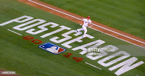 Mike Trout of the Los Angeles Angels of Anaheim runs past the Postseason signage painted on the field during the game against the Kansas City Royals...