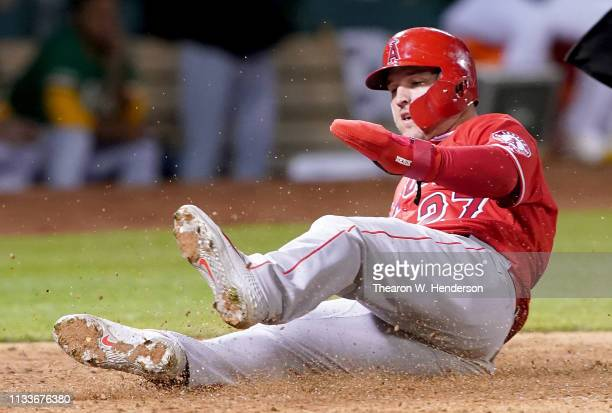 Mike Trout of the Los Angeles Angels of Anaheim scores against the Oakland Athletics in the top of the eighth inning of a Major League Baseball game...