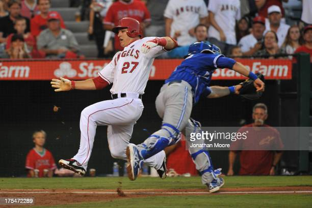 Mike Trout of the Los Angeles Angels of Anaheim scores past JP Arencibia of the Toronto Blue Jays on an RBI single hit by Howie Kendrick at the...