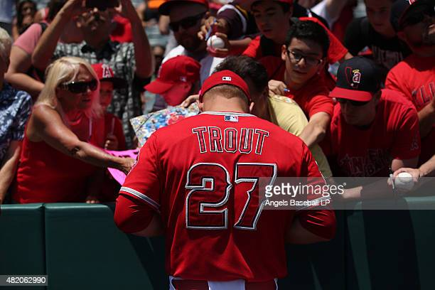 Mike Trout of the Los Angeles Angels of Anaheim signs autographs for fans before the game against the Minnesota Twins at Angel Stadium of Anaheim on...