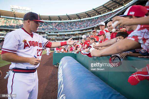 Mike Trout of the Los Angeles Angels of Anaheim signs autographs for young fans before the game against the Chicago White Sox at Angel Stadium of...