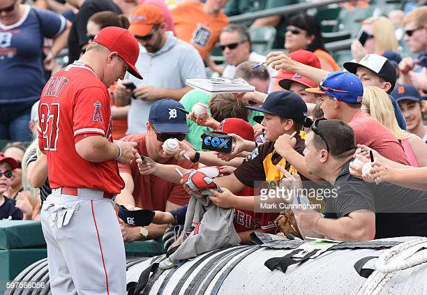 Mike Trout of the Los Angeles Angels of Anaheim signs autographs for fans prior to the game against the Detroit Tigers at Comerica Park on August 28...
