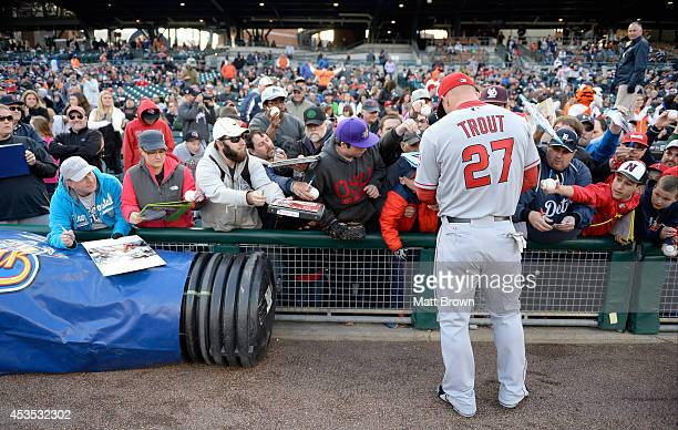 Mike Trout of the Los Angeles Angels of Anaheim signs autographs before the game against the Detroit Tigers at Comerica Park on April 18 2014 in...