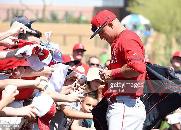 Mike Trout of the Los Angeles Angels of Anaheim signs autographs prior to a game against the Colorado Rockies at Salt River Fields at Talking Stick...