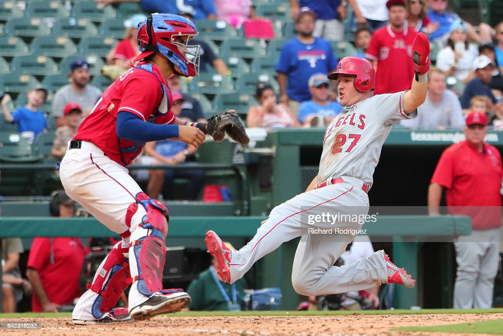 Mike Trout #27 of the Los Angeles Angels of Anaheim slides home to score on a double by Andrelton Simmons in the 9th inning as Robinson Chirinos #61 of the Texas Rangers waits for the throw home at Globe Life Park in Arlington on September 3, 2017 in Arlington, Texas.