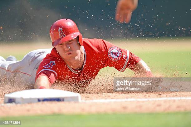 Mike Trout of the Los Angeles Angels of Anaheim slides safely into third base as he advances from first on a single to the outfield in the game...
