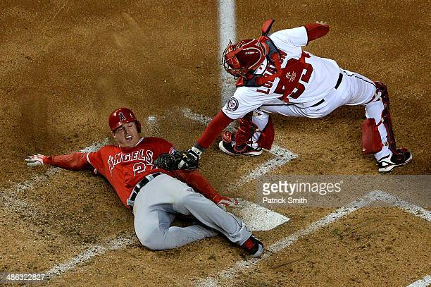 Mike Trout of the Los Angeles Angels of Anaheim slides safely into home plate as catcher Jose Lobaton of the Washington Nationals cannot make the tag...
