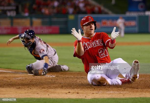 Mike Trout of the Los Angeles Angels of Anaheim slides safely past catcher Jason Castro of the Houston Astros and scores a run on a catching error by...