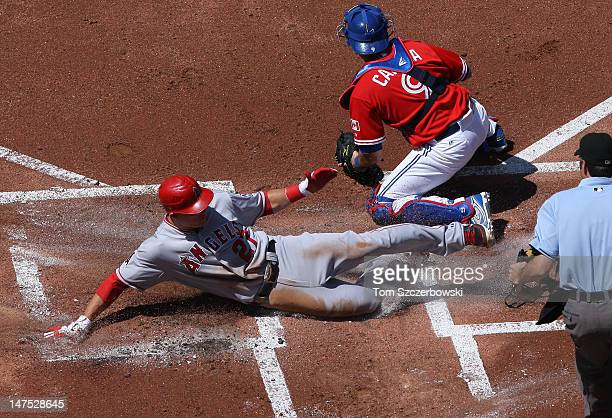 Mike Trout of the Los Angeles Angels of Anaheim slides to score a run in the 1st inning ahead of the tag of JP Arencibia of the Toronto Blue Jays on...
