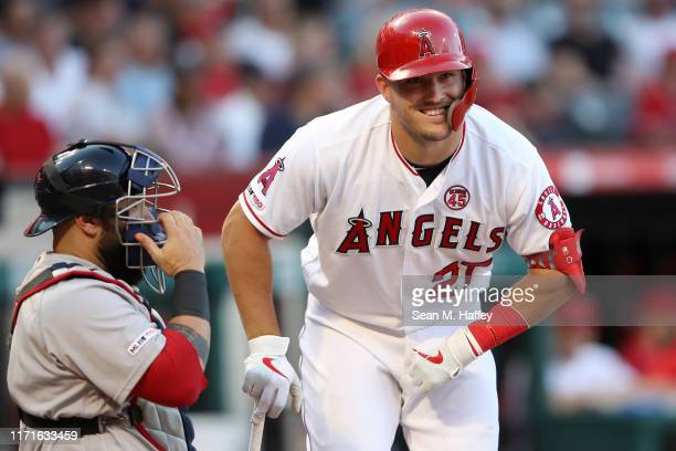 Mike Trout of the Los Angeles Angels of Anaheim talks with Sandy Leon of the Boston Red Sox during an at bat of a game at Angel Stadium of Anaheim on...