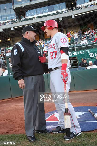 Mike Trout of the Los Angeles Angels of Anaheim talks with Umpire Dale Scott prior to the game against the Oakland Athletics at the OaklandAlameda...