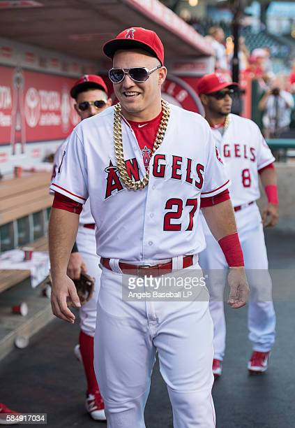 Mike Trout of the Los Angeles Angels of Anaheim wears a chain and sunglasses in the dugout before a presentation for David Ortiz' #34 of the Boston...